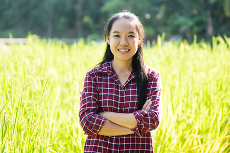 Asian woman farmer arms crossed in rice field