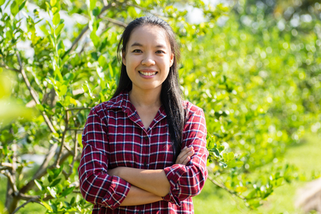 Asian woman farmer arms crossed in lime fruit garden Stock Photo