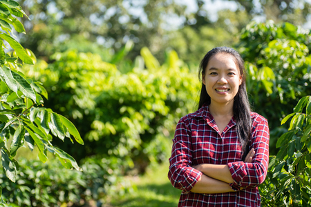Asian woman farmer arms crossed in longan orchard