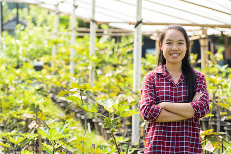 Asian woman farmer arms crossed in fig fruit garden