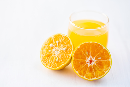 Tangerine orange fruit and juice on white table