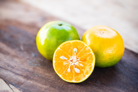 Green tangerine orange fruit on wooden table Stock Photo