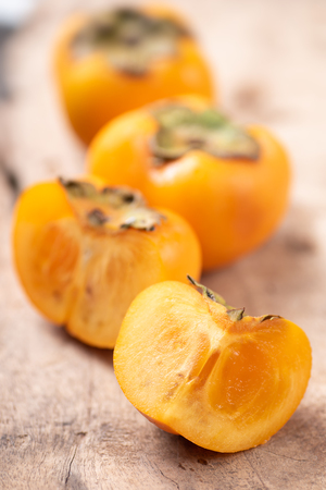 Persimmon fruit on wooden background, healthy fruit