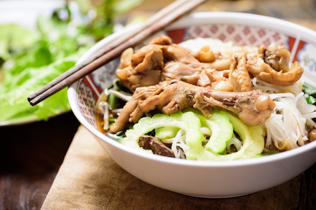 Rice noodles soup with stewed chicken wing and feet in a bowl with chopsticks Zdjęcie Seryjne