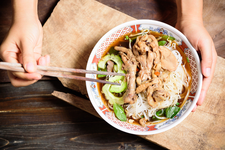 Rice noodles soup with stewed chicken wing and feet in a bowl and hand holding chopsticks for eating