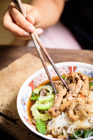 Hand holding chopsticks for eating rice noodles soup with stewed chicken wing and feet in a bowl Zdjęcie Seryjne