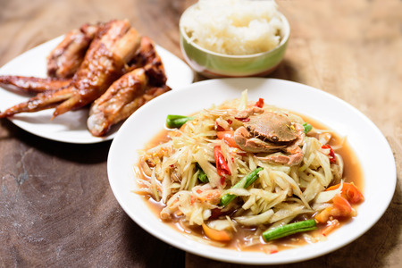 Spicy green papaya salad,grilled chicken wing and sticky rice. Thai food (Som Tum)