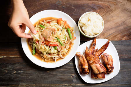 Hand holding sticky rice eating with spicy papaya salad and grilled chicken wing, Thai food (Som Tum) Zdjęcie Seryjne