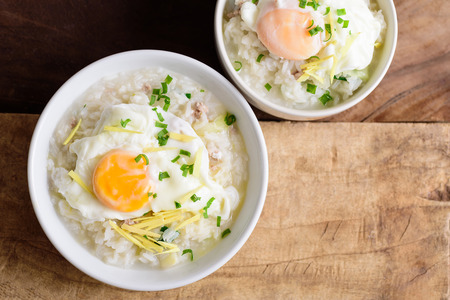 Thai rice soup or soft-boiled rice with pork and egg in the bowl on wooden background Zdjęcie Seryjne