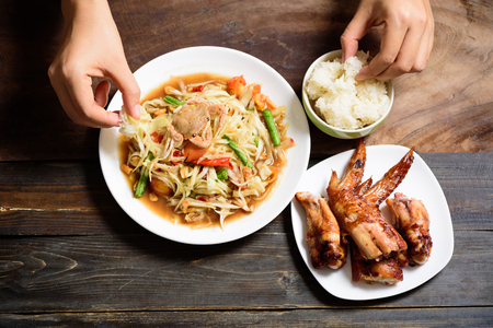 Hand holding sticky rice eating with spicy papaya salad and grilled chicken wing, Thai food (Som Tum)