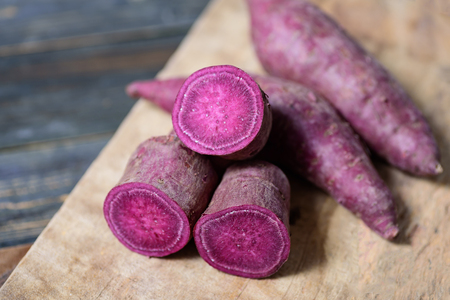 Purple sweet potatoes on wooden background
