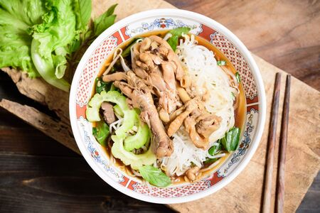 Rice noodles soup with stewed chicken wing and feet in a bowl with chopsticks Reklamní fotografie