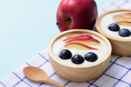 Yoghurt with apple and grape in a bowl on pastel background, healthy eating Фото со стока