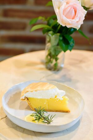 Piece of lemon meringue pie on white dish