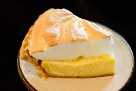Piece of coconut meringue pie on white dish