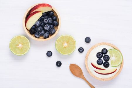 Yoghurt eating with blueberry, apple and lime on white background, healthy food Reklamní fotografie