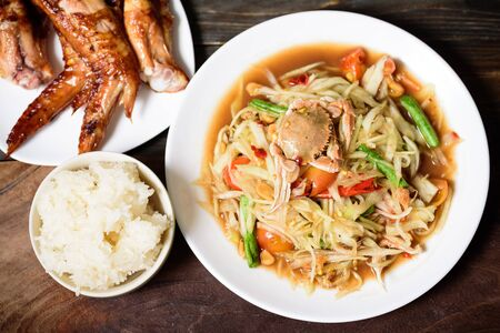 Spicy papaya salad,grilled chicken wing and sticky rice. Thai food (Som Tum)