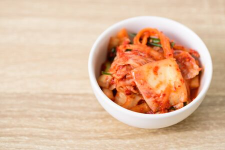 Kimchi cabbage in a bowl on wooden background, Korean food