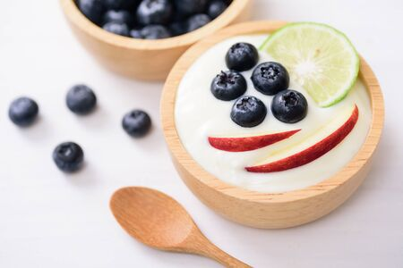 Yoghurt eating with blueberry, apple and lime, healthy food