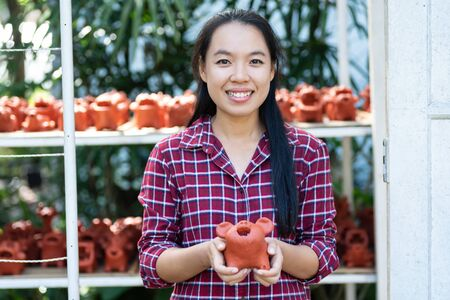 Asian woman holding animal baked clay doll in clay doll shop