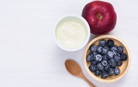 Yoghurt eating with blueberry and apple fruit on white background