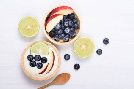 Yoghurt eating with blueberry, apple and lime on white background