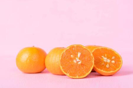Mandarin orange fruits on pink background