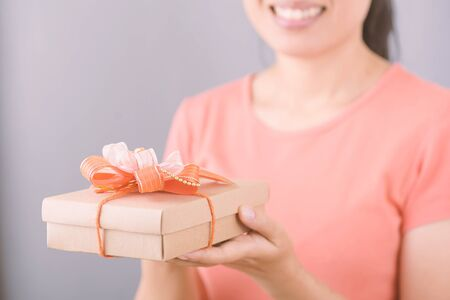 Woman holding gift box in hand for giving