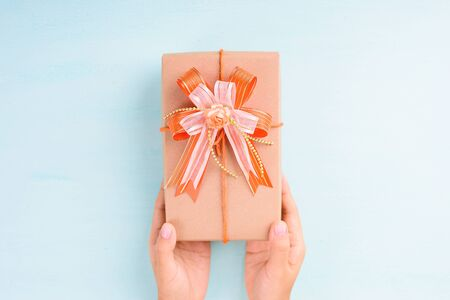 Gift box in hand for giving on pastel background