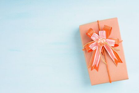 Gift box with orange ribbon and bow for giving on pastel background Zdjęcie Seryjne