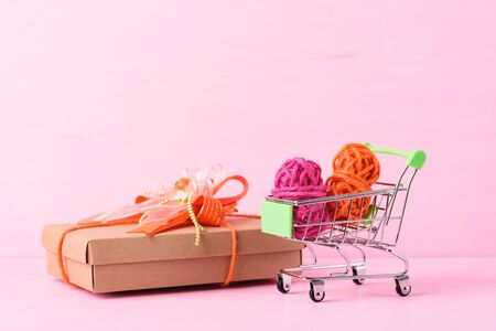 Shopping cart with ribbon and gift box on pink background