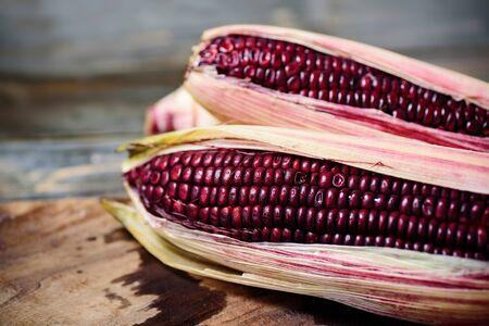 Fresh purple corn on wooden background Stockfoto