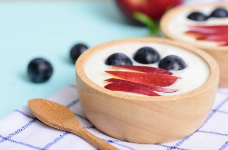 Yoghurt with apple and grape in a bowl on pastel background, healthy eating 版權商用圖片