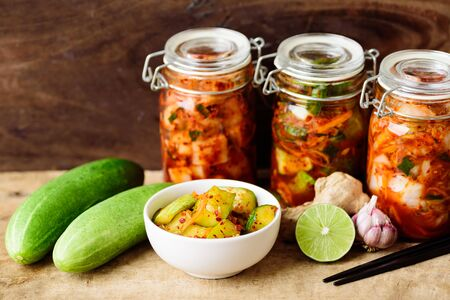 Kimchi cucumber in a bowl and jar on wooden background, Homemade Korean food