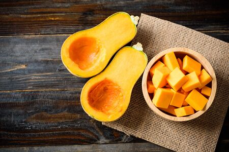 Half and slice butternut squash in bowl for cooking on wooden background, top view Stockfoto