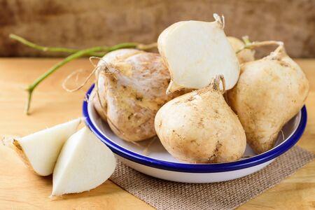 Fresh jicama or yam on wooden background