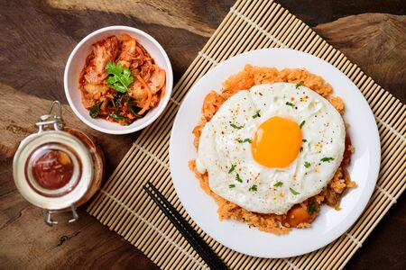 Kimchi fried rice with fried egg on top and kimchi cabbage in bowl and jar, Korean food