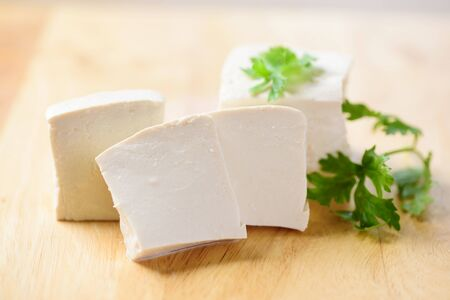 Sliced tofu for cooking on wooden cutting board