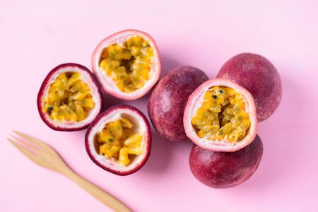 Fresh passion fruit and fork on pink background, tropical fruit