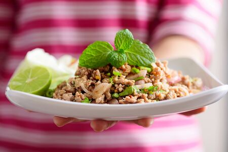 Thai food, spicy minced pork salad (Larb Moo) on white dish holding by hand