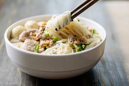 Rice noodles soup with pork and meat ball in a bowl with chopsticks on wooden table, Asian food, Thai style