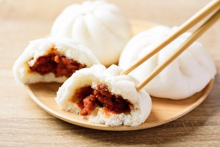 Steamed buns stuffed with red minced pork eating by using chopsticks, Asian food