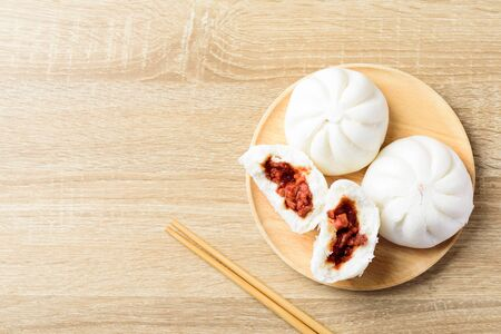 Steamed buns stuffed with red minced pork on wooden plate and chopsticks on wooden background, Asian food, Top view
