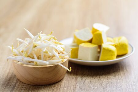 Fresh mung bean sprout in a bowl and sliced tofu on wooden background, food ingredient for Asian food