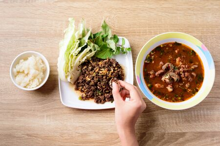 Traditional Northern Thai food, spicy minced pork salad (Larb Moo Kua) and spicy curry soup with beef guts (Kaeng Om Nua) eating with sticky rice by hand Stockfoto