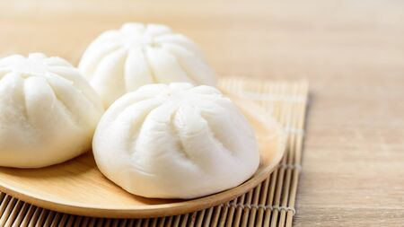 Steamed buns stuffed with minced pork on wooden plate, Asian food