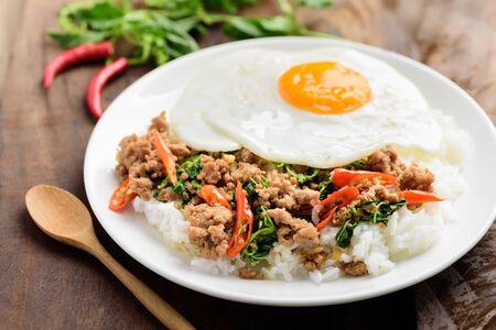 Thai food, stir-fried holy basil with minced pork and fried egg (Pad Kaprao Moo Kai Dao) on wooden background