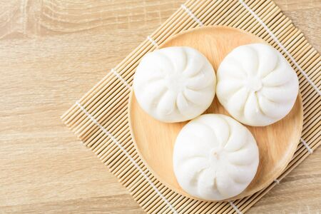 Steamed buns stuffed with minced pork and salted egg on wooden plate, Asian food