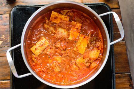 Kimchi soup with tofu cooking in hot pot, Korean food (Kimchi Jjigae)