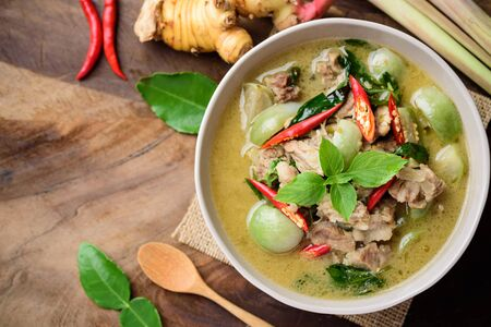 Thai food, Green curry with pork (Kang Keaw Wan) in a bowl with ingredients on  wooden background